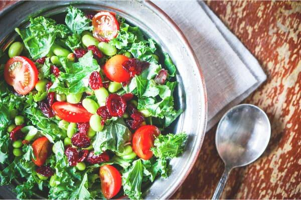 vegan kale salad with garden tomatoes and cranberries on a wood background
