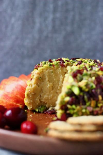 sweet cashew cheese ball covered in dried cranberries and pistachios from rhiansrecipes