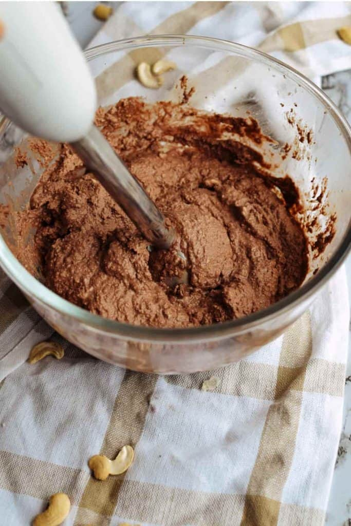 using an immersion blender to blend the date chocolate cake filling