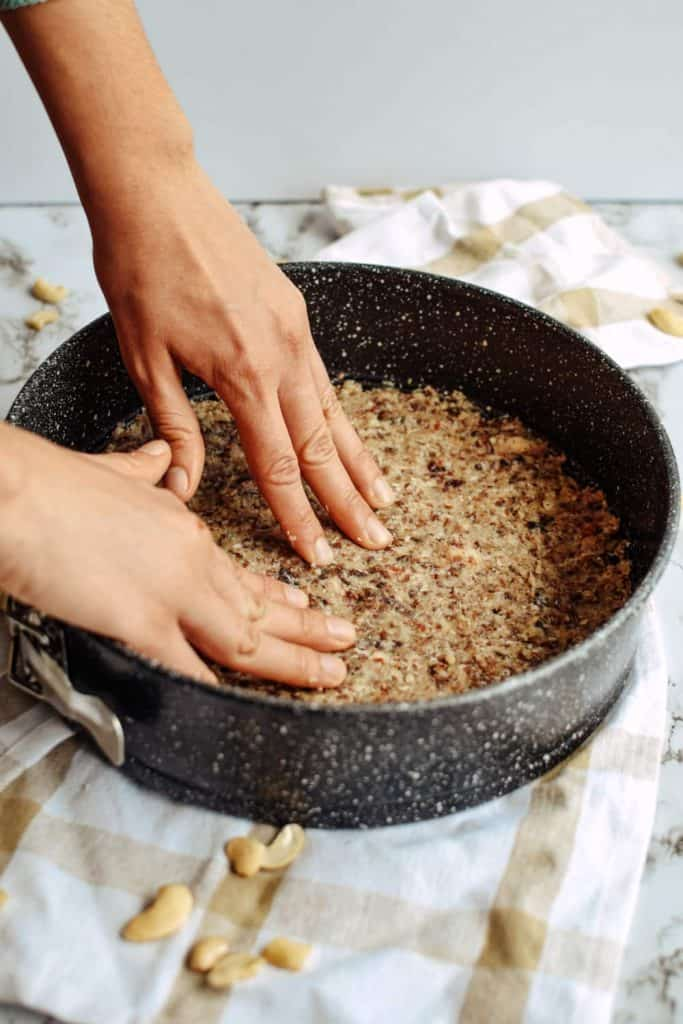 pressing the raw nut crust into a cake pan