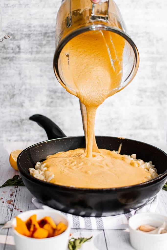 pouring pumpkin cheese sauce onto cooked macaroni pasta in pan